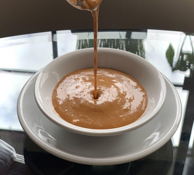 Crazy good no-peanut sauce, vegan, being pored into a small white dish