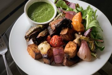 Marinated Vegan kebobs plated with cilantro pesto and mixed greens