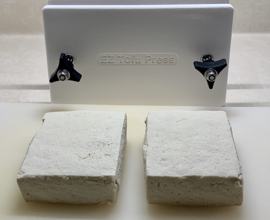 Two blocks of tofu, next to a tofu press to be used in Vegan Marinated Meal-Prep Kebobs (oven or grill)