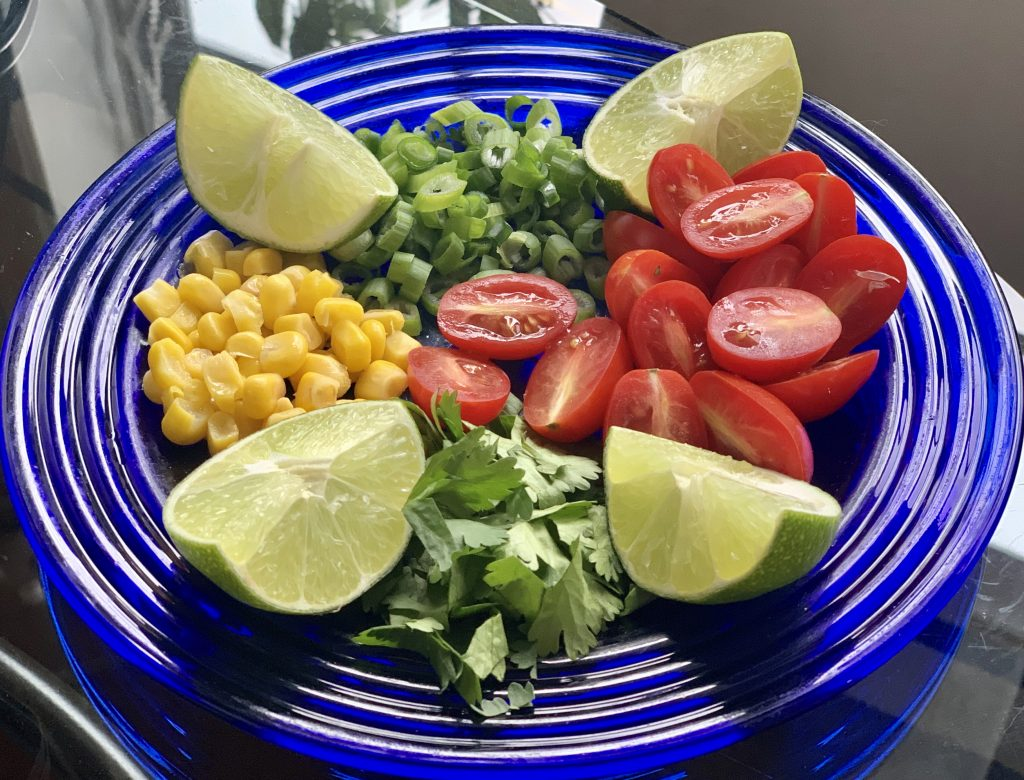 garnishes for Creamy Vegan Instant Pot Corn Chowder plated on a blue plate
