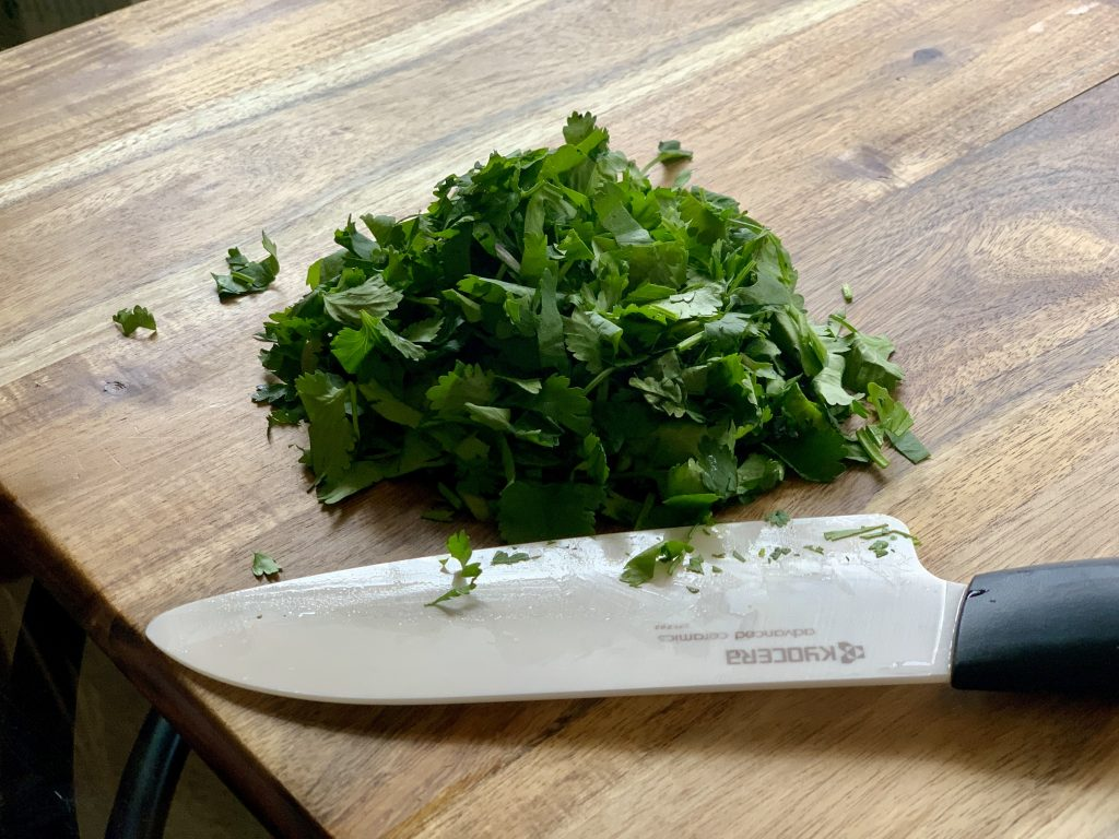 chopped cilantro on a wooden cutting board for Chipotle-Style Corn Salsa