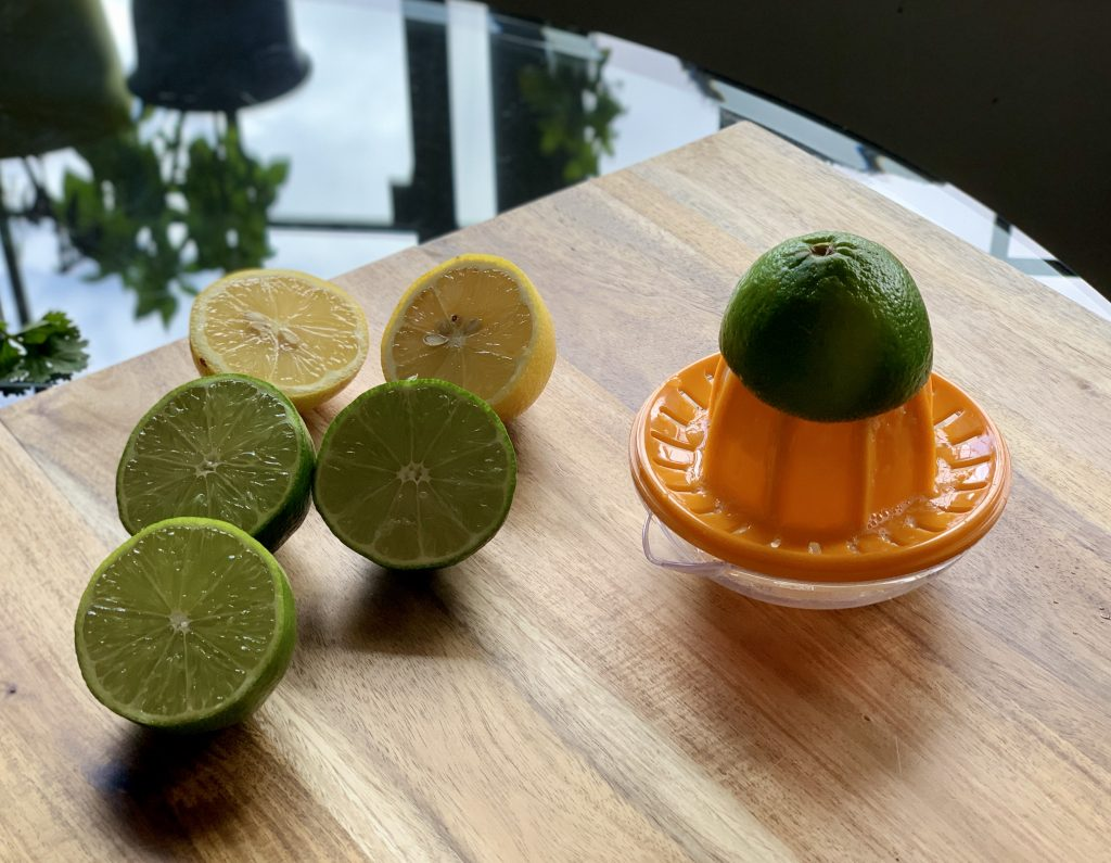 Juicing lemons and limes with a small hand juicer for Chipotle-Style Corn Salsa