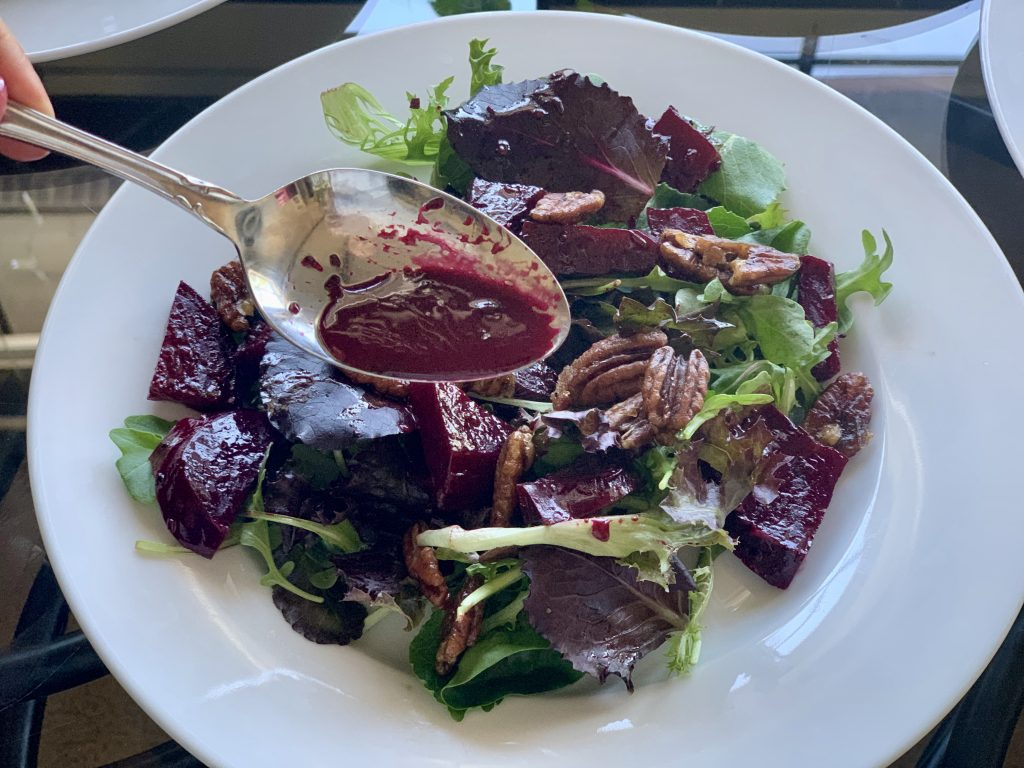 Drizzling the juice from the beets onto the salad